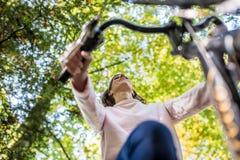 妇女在秋天的骑一辆自行车 库存照片
