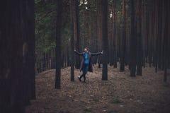 妇女在秋天黑暗的森林里 免版税库存照片