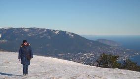 妇女在积雪的山高原去 股票录像