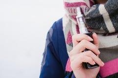 妇女在积雪的河附近抽在街道的一根电子香烟 库存照片