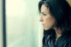 妇女在窗口前面站立 免版税库存照片