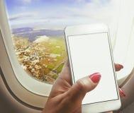 妇女在窗口附近坐,拿着在船上运转飞机的智能手机 库存照片