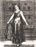 妇女在站立在地毯前面的吉普赛服装穿戴了 图库摄影