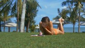 妇女在笔记本写在新鲜的草在公园 股票录像