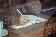 妇女在笔记本的手文字在咖啡馆在雨天 库存照片
