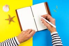 妇女在笔记本的手文字在蓝色和黄色背景 库存图片