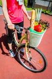 妇女在篮子自行车的winth杂货特写镜头  免版税库存图片