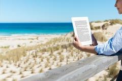 妇女在篱芭的读书E读者在海滩 免版税库存照片