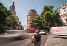 妇女在繁忙的伦敦交叉点站立。 库存图片