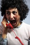 妇女在红色电话发狂 免版税库存照片