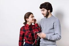 妇女在红色被检查的灰色毛线衣的拿着智能手机听到音乐的衬衣和有胡子的人穿戴了与耳机 免版税库存图片