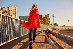 妇女在红色雨衣的超级英雄赛跑者跑步 图库摄影