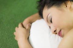 妇女在绿草,放下在绿草的一名美丽和梦想的泰国妇女睡觉,放松 库存图片