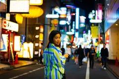 妇女在网上购物在夜街道在城市 免版税库存照片