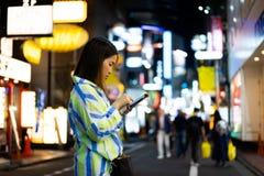 妇女在网上购物在夜街道在城市 图库摄影