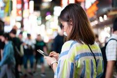 妇女在网上购物在夜街道在城市 免版税图库摄影