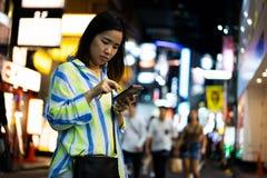 妇女在网上购物在夜街道在城市 库存照片