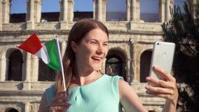 妇女在罗马斗兽场附近做在机动性的selfie在罗马,意大利 在慢动作的少年波浪意大利旗子 股票视频