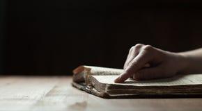 妇女在老圣经书的手指新闻 免版税库存图片