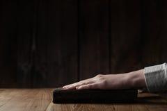 妇女在老圣经书的手指新闻 免版税图库摄影