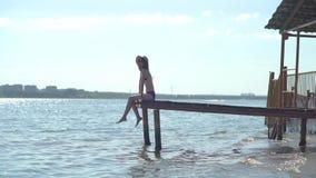 妇女在背景中放松坐在一只木跳船边缘,腿在水表面附近摇摆 股票录像