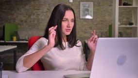 妇女在膝上型计算机前面的办公室,在屏幕上观看并且做她的但愿的,盼望运气 股票录像