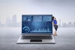 妇女在膝上型计算机和谈话倾斜在电话 库存图片