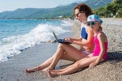 妇女在膝上型计算机在海滩,自由空间的工作狂工作 家庭度假、母亲和女儿坐海滩 免版税库存图片
