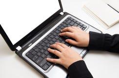 妇女在膝上型计算机的手印刷品 图库摄影