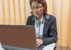妇女在膝上型计算机的手印刷品 免版税库存图片