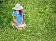 妇女在自然读一本书 免版税库存照片