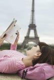 妇女在艾菲尔铁塔前面的阅读书 库存图片