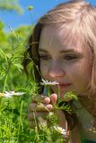 妇女在花嗅到在公园 免版税库存图片