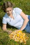 妇女在草坪位于在黄蘑菇附近 库存图片