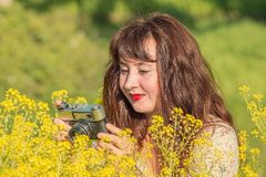 妇女在草甸的射击花 库存图片