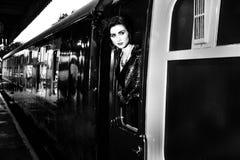 妇女在葡萄酒倾斜在火车窗口外面和送飞吻的晚礼服穿戴了 免版税库存照片