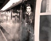 妇女在葡萄酒倾斜在火车窗口外面和送飞吻的晚礼服穿戴了 库存图片