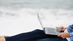 妇女在蓝色牛仔裤和偶然衬衣坐在接近的看法与数字技术膝上型计算机设备 股票录像