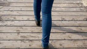 妇女在蓝色牛仔裤的` s腿在黑秋天鞋子 股票视频