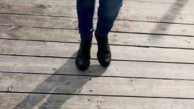 妇女在蓝色牛仔裤的` s腿在黑秋天鞋子 股票录像