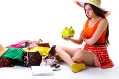 妇女在被过度充填的手提箱附近坐 免版税库存图片