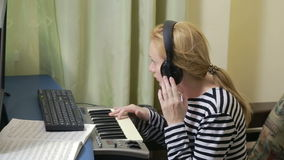 妇女在计算机写音乐 数字式钢琴密地键盘 影视素材