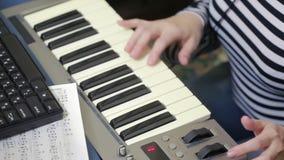 妇女在计算机写音乐 数字式钢琴密地键盘 股票录像