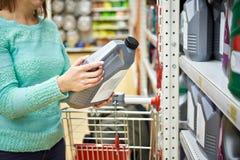 妇女在超级市场买机器润滑油 库存照片