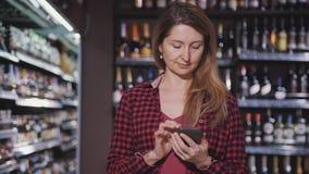 妇女在超级市场在关于食物的互联网信息单独站立并且浏览 影视素材