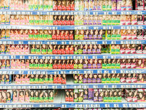 妇女在超级市场架子的染发剂产品 免版税库存图片