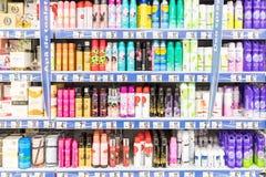 妇女在超级市场立场的防臭剂浪花 免版税库存照片