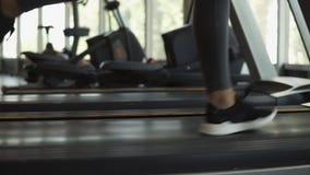 妇女在跑在健身俱乐部的一辆踏车的snakers的` s脚特写镜头英尺长度  灰色绑腿的白肤金发的妇女和 股票录像