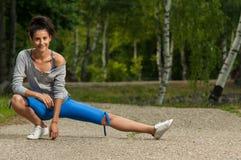 妇女在跑步前温暖她的腿肌肉 库存图片