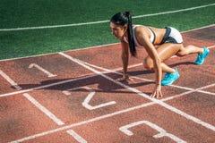 妇女在跑的一个低开始站立 免版税库存图片
